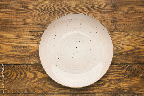 Empty pink ceramic plate on woden table