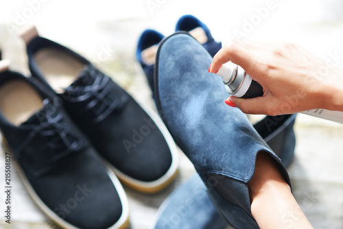 Shoes care concept with woman hands spraying leather shoe