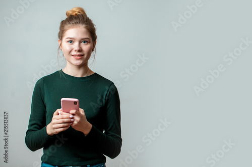 Portrait of a smiling pretty casual woman holding smartphone over grey background