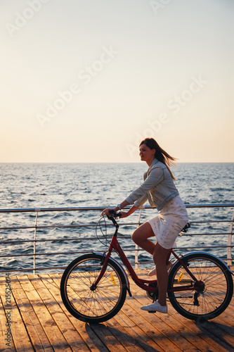 Fotobehang Fiets Young woman cycling at the beach at sunrise sky at wooden deck summer time