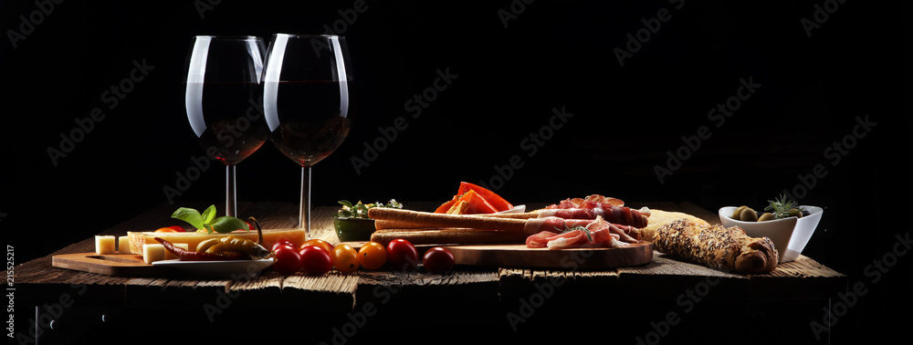 Fototapety, obrazy: Italian antipasti wine snacks set. Cheese variety, Mediterranean olives, crudo, Prosciutto di Parma, salami and wine in glasses over wooden grunge background.