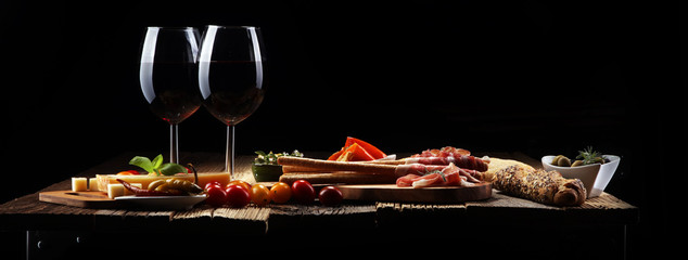 Panel SzklanyItalian antipasti wine snacks set. Cheese variety, Mediterranean olives, crudo, Prosciutto di Parma, salami and wine in glasses over wooden grunge background.