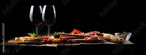 Fototapeta Italian antipasti wine snacks set. Cheese variety, Mediterranean olives, crudo, Prosciutto di Parma, salami and wine in glasses over wooden grunge background. obraz