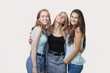 Three happy girls dressed in casual style pose in the studio