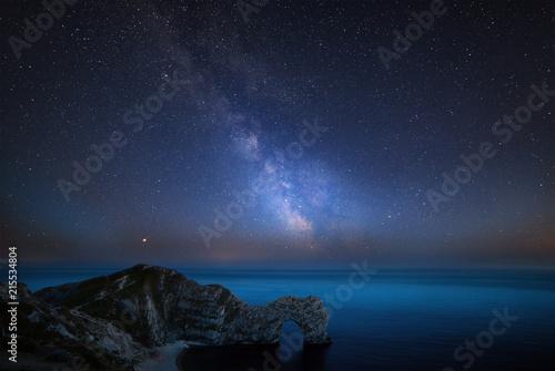 Foto op Aluminium Nachtblauw Beautiful vibrant image of Milky Way galaxy over sea landscape in Dorset England