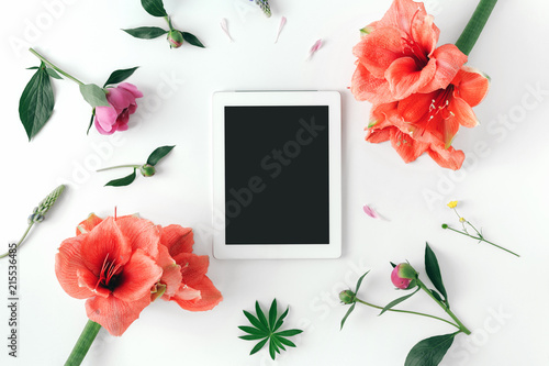 Flat lay white tablet blank desktop screen flowers top view
