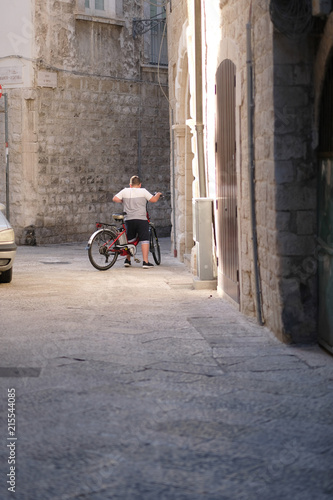 A boy with a bicycle on a narrow street of an ancient city. Italy