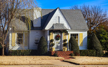 Cute Cottage With Yellow Shutters And Christmas Wreath And Garland Decorating Entrance