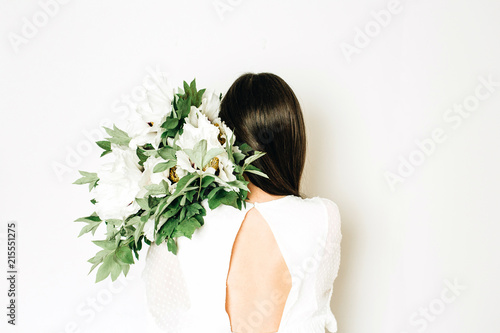 Young woman holding white peonies bouquet on white background.