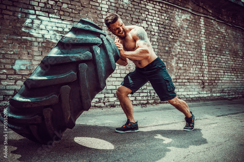 Obraz na plátně  Muscular bearded tattooed fitness shirtless man moving large tire in street gym