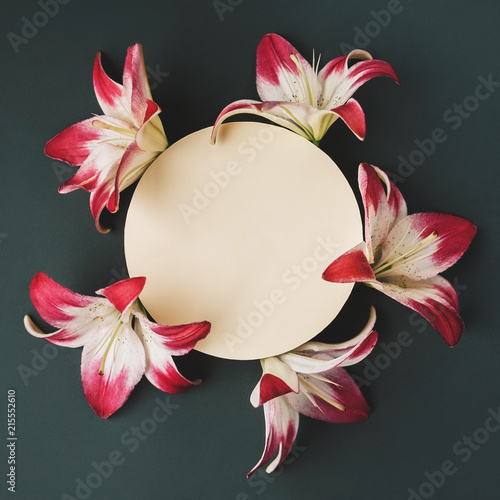 Tuinposter Bloemen Buds of white and pink lilies lined in a circle on dark background. Copy space. Top view.