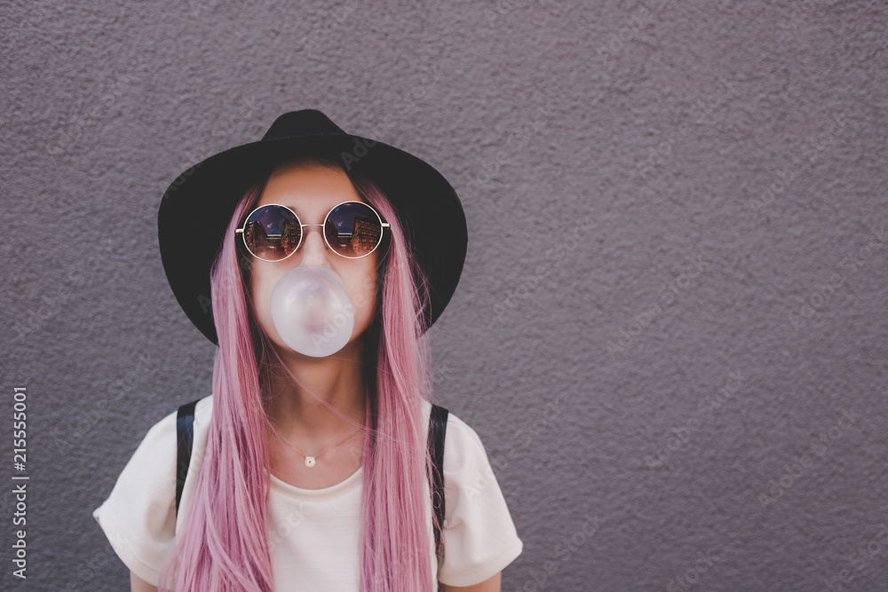 Fototapeta Young hipster woman with long pink hair blowing a bubble with bubble gum.