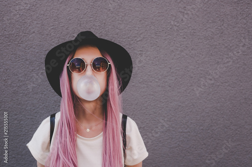 Papel de parede Young hipster woman with long pink hair blowing a bubble with bubble gum