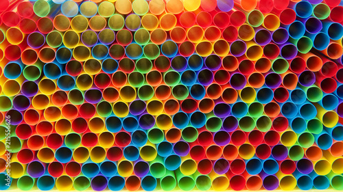 Hundreds of colorful plastic straws laying facing forwards opening towards viewer, laying on yellow surface. Many cities are now banning single use plastic straws.