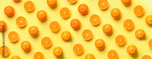 Deurstickers Pop Art Fruit pattern of fresh orange slices on yellow background. Top view. Copy Space. Pop art design, creative summer concept. Half of citrus in minimal flat lay style. Banner.