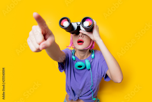 Young style girl in purple clothes with binoculars on yellow background.  Clothes in 1980s style