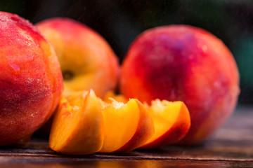 Fototapeta na wymiar Fresh ripe peaches and slices on wooden table