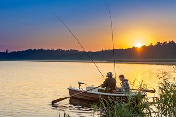 ojciec i syn złapać ryby z łodzi o zachodzie słońca