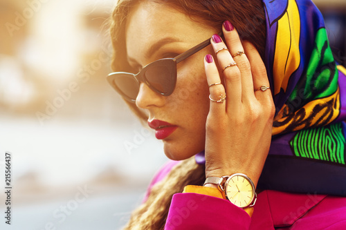 Outdoor close up fashion portrait of young beautiful woman with freckles,  wearing sunglasses, wrist, watch, a lot of rings, colorful kerchief, posing in street of city. Copy, empty space for text