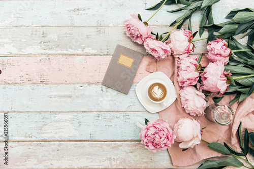 Photo Flat lay cup of coffee and peonies on shabby chic background.