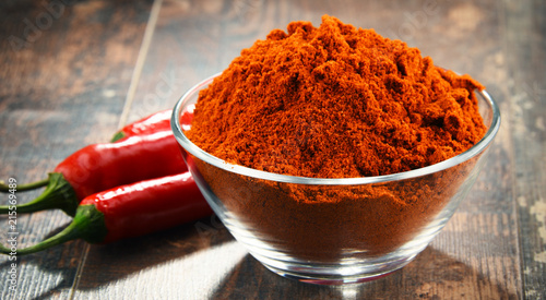 Composition with bowl of chili powder on wooden table