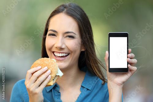 Woman holding a hamburger showing a phone screen