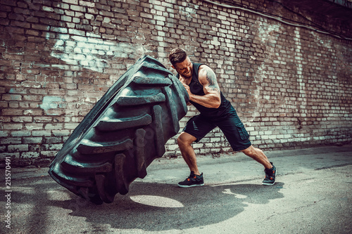 Obraz na plátně  Muscular bearded tattooed fitness man moving large tire in street gym