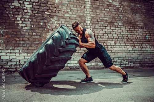 Valokuva Muscular bearded tattooed fitness man moving large tire in street gym