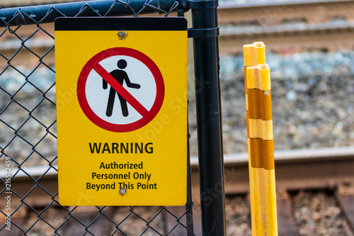 Fotografie, Obraz  Warning authorized personnel sign on a chain link fence