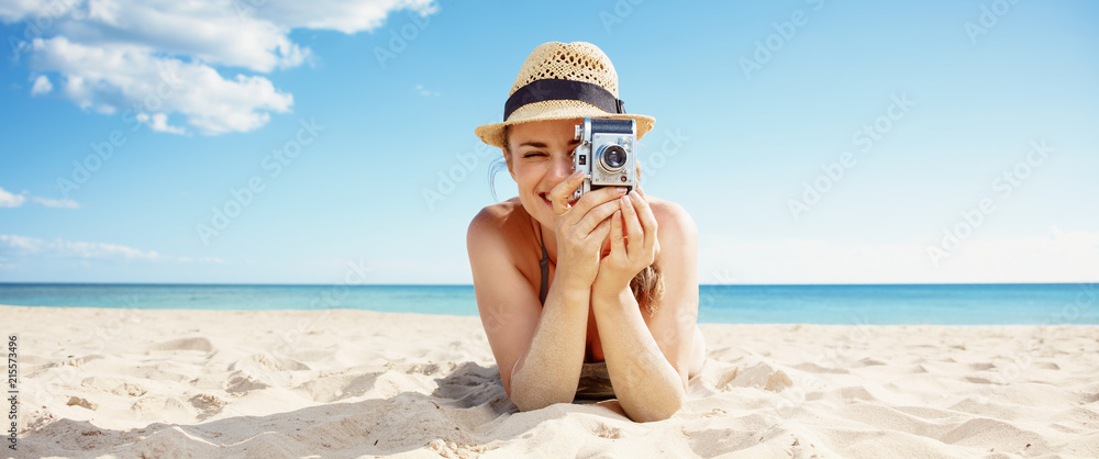 Fototapety, obrazy: happy woman taking photo with retro photo camera on seacoast