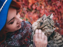 Beautiful Red-haired Woman In Blue Hat And Leather Jacket Walking With Cat In Autumn Red Park.