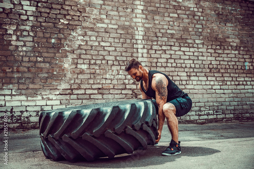 Muscular bearded tattooed fitness man moving large tire in street gym Canvas-taulu
