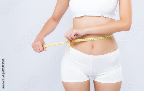 Obraz Asian woman diet and slim with measuring waist for weight isolated on white background, girl have cellulite and calories loss with tape measure, health and wellness concept. - fototapety do salonu