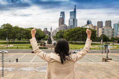Photo  A young business woman flexing and imitating the famous Rocky pose as a symbol o