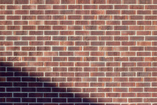 Traditional Running Bond Pattern Brown Brick Wall Background With Encroaching Shade In Lower Left Angle
