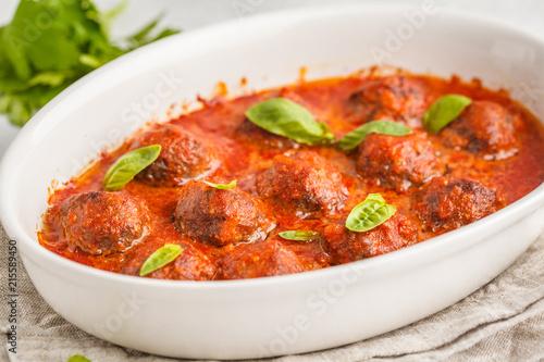 Photo sur Aluminium Plat cuisine Meatballs in tomato sauce in a white dish.