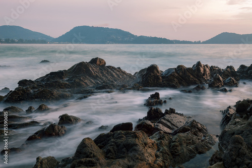 Photographie  Long exposure image of Dramatic sky and wave seascape with rock in sunset scenery background