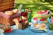 Fruit, Bread, Honey And Ice Cream On Picnic Table