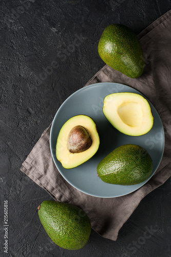 Some fruit of avocado whole and half on plate