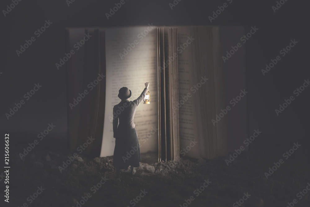 Fototapeta Curious woman illuminates with a lantern a giant book at night