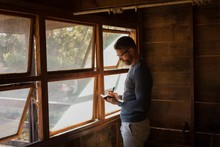 Man Writing In Diary While Standing Near Window