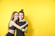 canvas print picture - Portrait of two fitness females on yellow background. Young women friends standing against wall and smiling