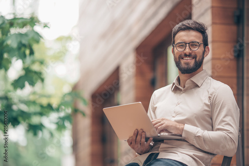 Obraz Smiling man with laptop outdoors - fototapety do salonu
