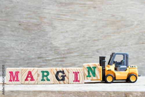 Fotografie, Obraz  Toy forklift hold letter block N to complete word margin on wood background