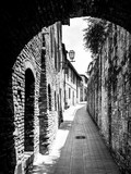 Fototapeta Uliczki - Picturesque medieval narrow street of San Gimignano old town, Tuscany, Italy. Black and white image.