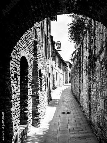 Malownicza średniowieczna wąska ulica San Gimignano stary miasteczko, Tuscany, Włochy. Obraz czarno-biały.