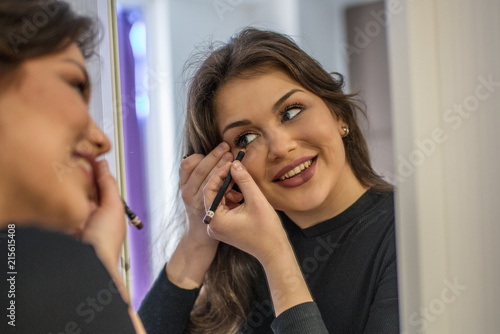 Happy beautiful smile young brunette woman relaxed doing her make up in front of a mirror