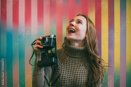 Happy young woman holding a vintage camera in a colorful