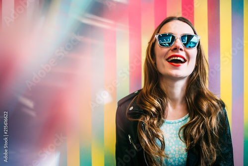 Happy young blonde woman in a colorful background