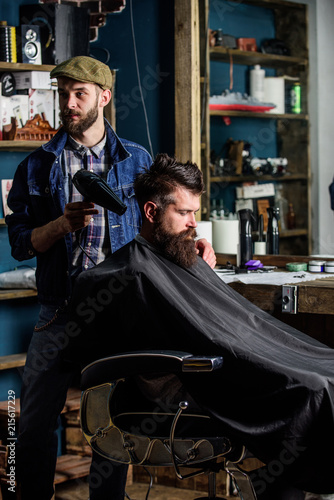 Vászonkép Barber with hairdryer works on hairstyle for bearded man barbershop background